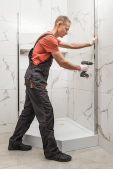 Travailleur installe un profilé métallique de la cabine de douche avec un tournevis.