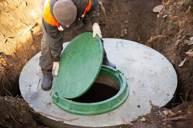 Un travailleur installe un regard d'égout sur une fosse septique en anneaux de béton construction d'égouts