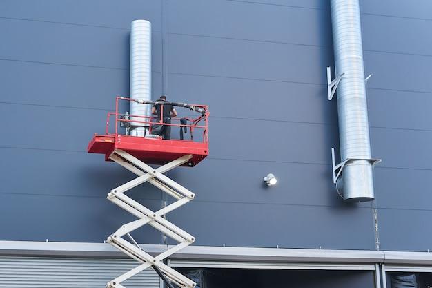 Le travailleur installe un système de ventilation sur la façade d'un bâtiment à l'aide d'un élévateur à ciseaux