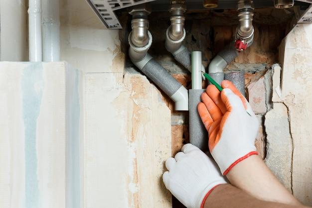 Un travailleur installe les tuyaux de la chaudière à gaz.