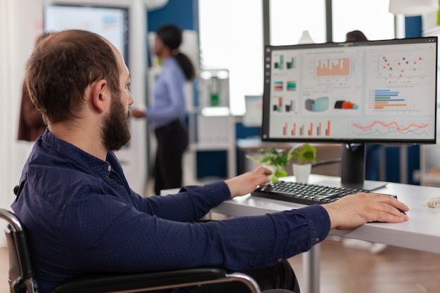 Travailleur invalide handicapé travaillant à l'ordinateur