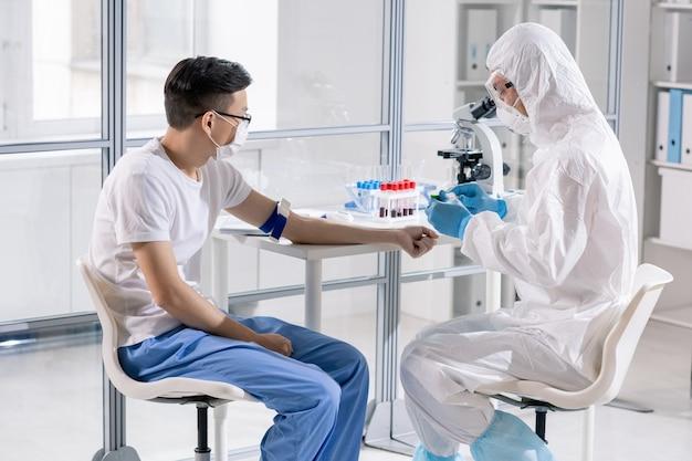 Travailleur de laboratoire médical en vêtements de protection va prendre le sang d'un jeune homme chinois pour diagnostiquer une maladie