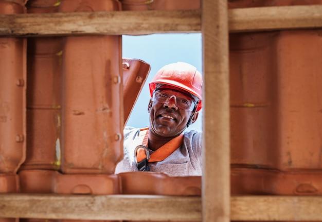Travailleur latin installant des tuiles de toiture en céramique jaune montées sur des planches de bois couvrant le toit d'un immeuble résidentiel en construction.