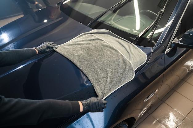 Le travailleur de lavage de voiture essuie la voiture après le lavage avec une serviette en microfibre.