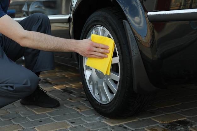 Un travailleur de lavage de voiture lave les roues d'une voiture