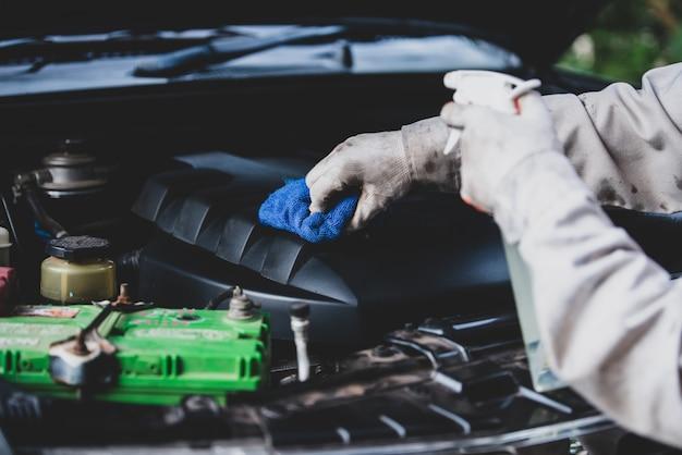 Travailleur de lavage de voiture vêtu d'un uniforme blanc tenant une éponge pour nettoyer la voiture dans le centre de lavage de voiture, concept pour l'industrie de l'entretien automobile.