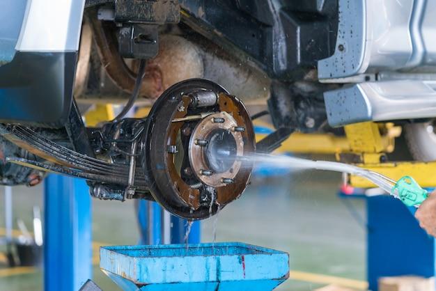Le travailleur lavant le frein à tambour d'une voiture sous haute pression.