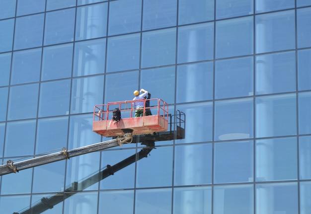 Travailleur lave les fenêtres sur la façade de verre d'un gratte-ciel