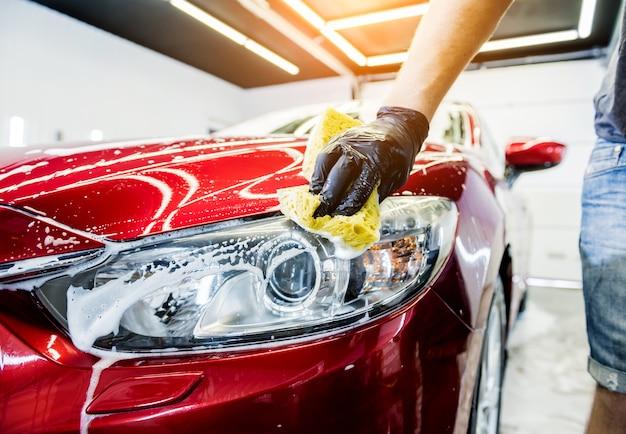 Travailleur lave-voiture rouge avec une éponge sur un lave-auto.