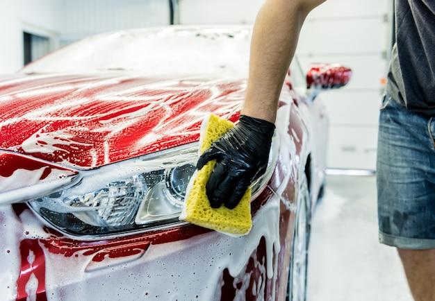Travailleur lave voiture rouge avec une éponge sur un lave-auto.