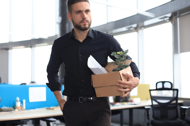 Un travailleur licencié triste prend ses fournitures de bureau avec lui du bureau.