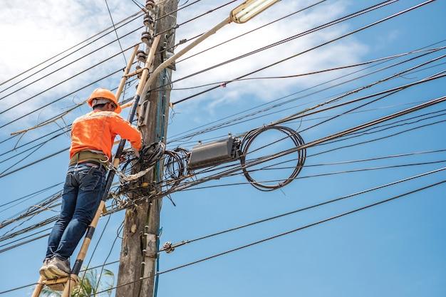 Travailleur de ligne électrique grimper une échelle en bambou pour réparer le fil