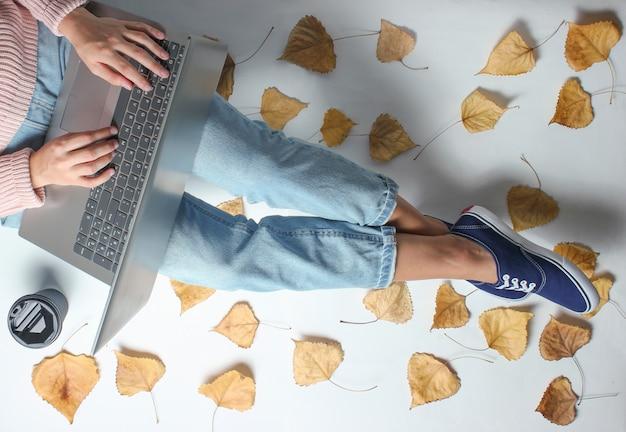 Travailleur en ligne sur le lieu de travail. fragment de jambes féminines en jeans et baskets. une femme est assise parmi les feuilles mortes et un ordinateur portable. concept indépendant. travail à la maison.
