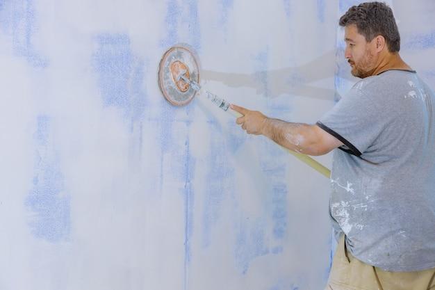 Travailleur de lissage et de finition du mur avec ponçage de la plaque de plâtre dans les cloisons sèches