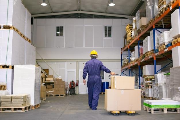 Travailleur logistique senior en casque et uniforme marchant dans l'entrepôt, cric de palette à roues. vue arrière, pleine longueur. concept de travail et de logistique