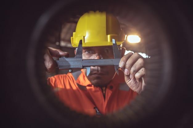 Le travailleur manipule le métal au tour turner mesure les dimensions de la pièce métallique avec un pied à coulisse en uniforme avec sécurité