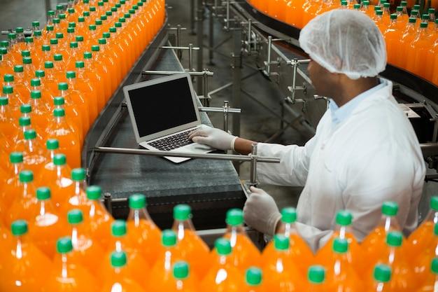 Travailleur masculin à l'aide d'un ordinateur portable au milieu de la chaîne de production dans l'usine de jus