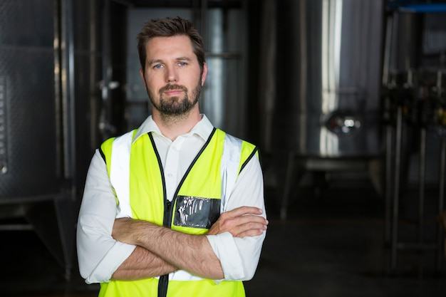 Travailleur masculin avec les bras croisés debout en usine