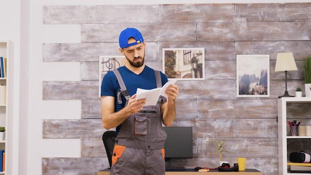 Un travailleur masculin en combinaison est confus en lisant les instructions pour l'assemblage des meubles et en partant de l'appartement.