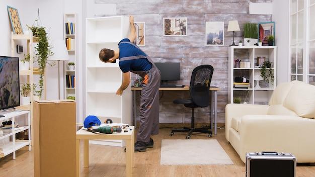 Un travailleur masculin en combinaison ramasse les meubles assemblés dans l'appartement des propriétaires.