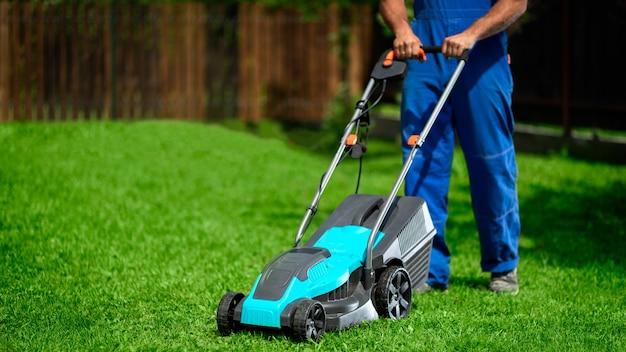 Travailleur masculin dans la rue travaillant à tondre la pelouse à l'aide d'une tondeuse à gazon moderne