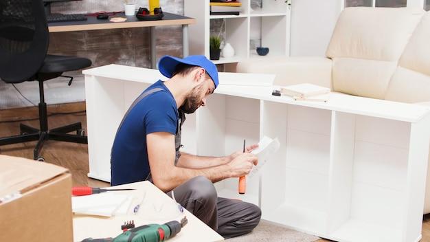 Un travailleur masculin écoute des instructions sur un téléphone portable pour l'assemblage de meubles.