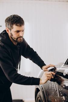 Travailleur masculin enveloppant une voiture avec une feuille de protection
