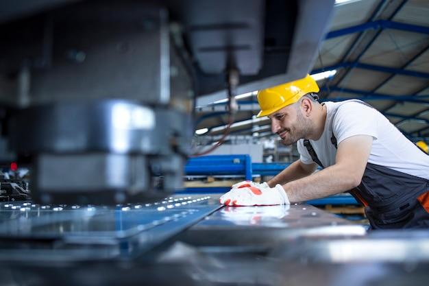 Travailleur masculin avec équipement de protection et casque travaillant sur une machine industrielle dans la ligne de production en usine.