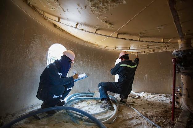 Le travailleur masculin est destiné à l'inspection de l'épaisseur par ultrasons sous la zone du trou de la jupe chimique du réservoir inférieur, espace confiné
