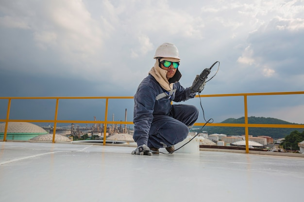 Le travailleur masculin est pour l'inspection par ultrasons de la plaque de toit en haut du réservoir de stockage