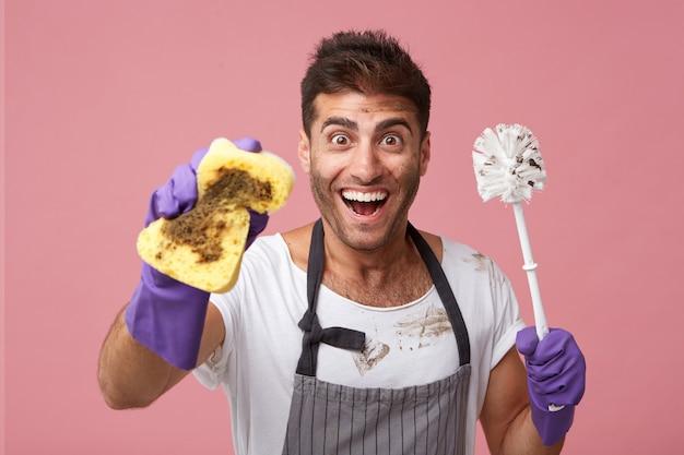 Travailleur masculin excité portant un tablier et des gants de protection