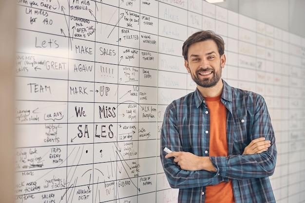 Travailleur masculin gai avec les bras croisés regardant la caméra et souriant en se tenant debout près du tableau blanc