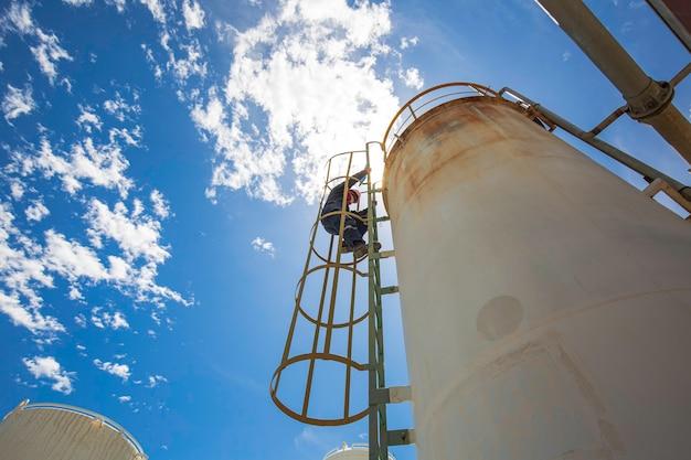 Le travailleur masculin en haut de l'échelle est destiné à l'inspection par ultrasons de la plaque de coque d'épaisseur du produit chimique du réservoir de stockage.
