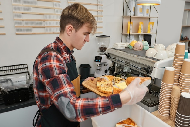 Un travailleur masculin heureux en tablier vend des produits de boulangerie frais dans un café ou à la cafétéria