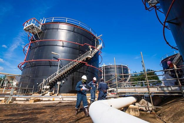 Un travailleur masculin inspecte le pipeline visuel et le pétrole brut du réservoir de stockage