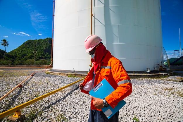Travailleur masculin inspection visuelle du réservoir de pétrole et de gaz.