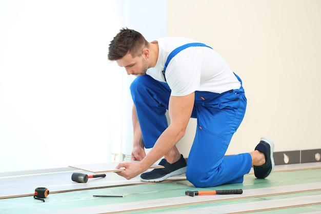 Travailleur masculin installant le plancher stratifié