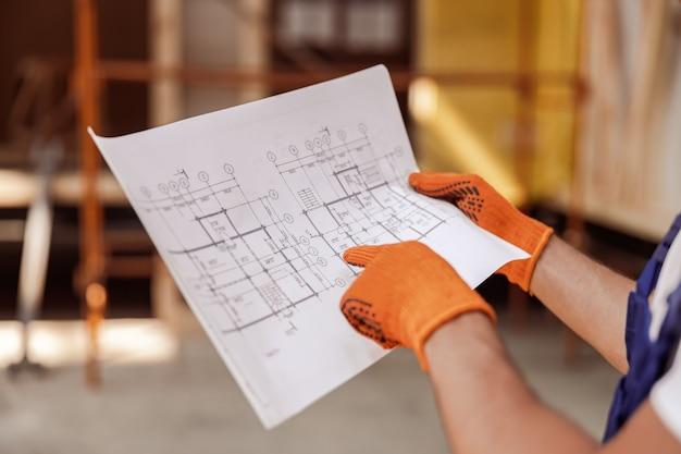 Travailleur masculin mains dans des gants tenant un plan architectural
