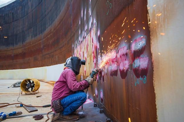 Un travailleur masculin meulant sur une plaque d'acier avec un éclair d'étincelles en gros plan porte des gants de protection à l'huile à l'intérieur d'espaces confinés.
