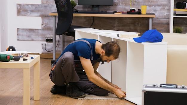 Travailleur masculin montrant le signe du pouce après avoir monté une étagère sur de nouveaux meubles pour les propriétaires de maison.