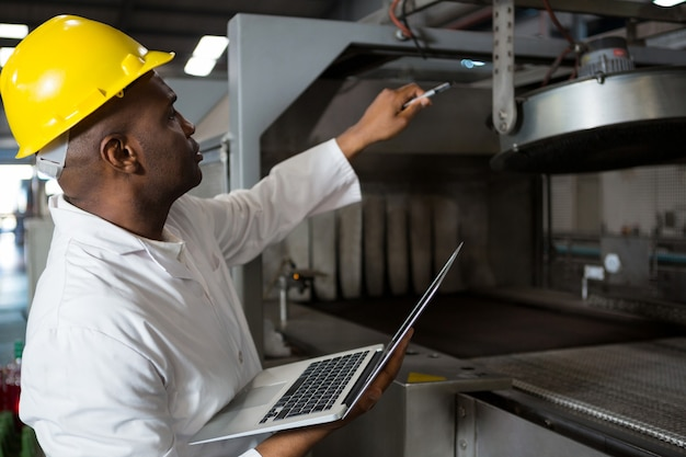 Travailleur masculin portant une blouse de laboratoire tout en utilisant un ordinateur portable