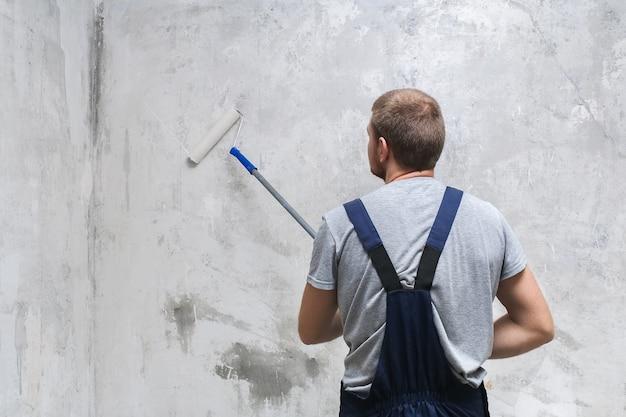 Un travailleur masculin prépare le mur avec un rouleau pour une meilleure adhérence.