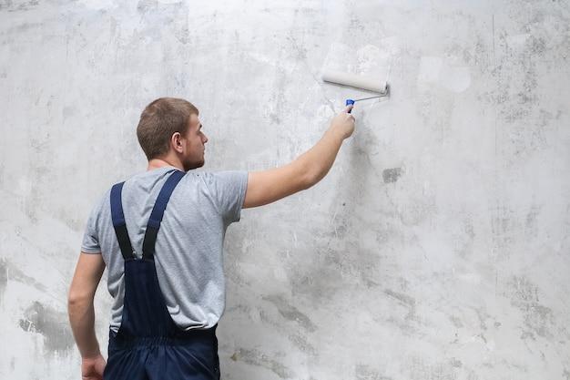 Le travailleur masculin prépare le mur avec un rouleau pour une meilleure adhérence