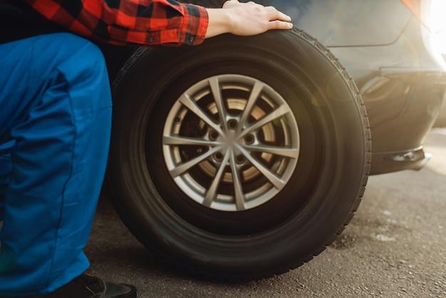 Travailleur masculin en problème de fixation uniforme avec pneu