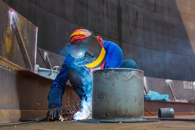 Travailleur masculin de soudage partie d'arc métallique dans la construction d'un pipeline de buse de réservoir de pétrole et de gaz de stockage du toit du réservoir supérieur