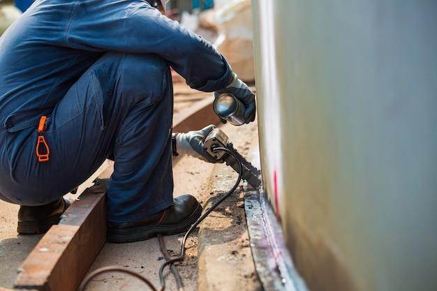 Travailleur masculin test réservoir en acier soudure bout à bout plaque de coque de carbone de réservoir de stockage fond d'huile contraste blanc de test de champ magnétique