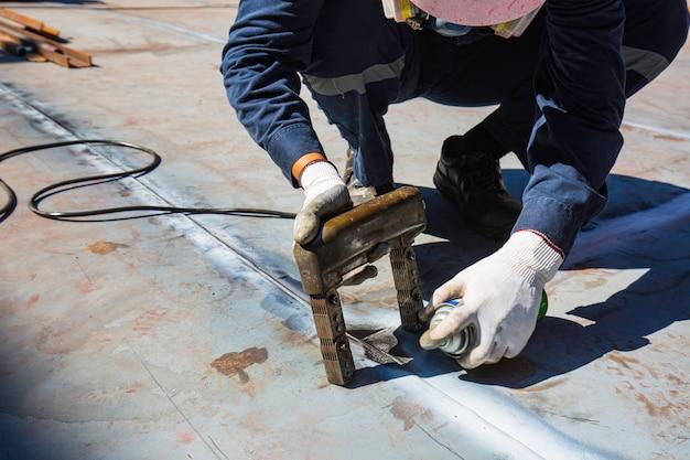Travailleur masculin test réservoir en acier soudure bout à bout plaque inférieure en carbone du réservoir de stockage fond d'huile contraste blanc du test de champ magnétique