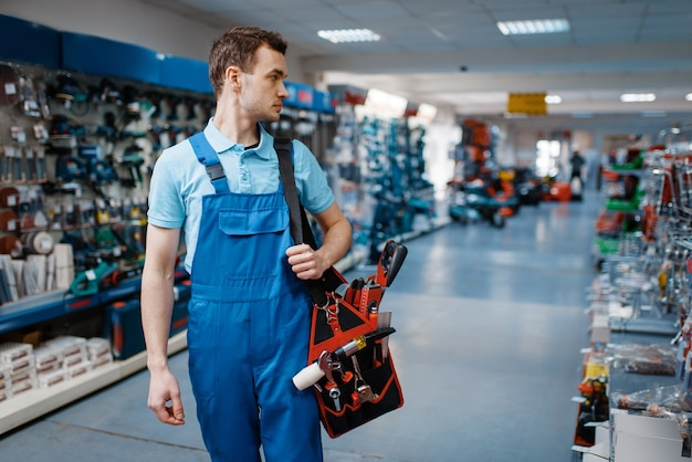 Travailleur masculin en uniforme détient la boîte à outils dans le magasin d'outils. choix de matériel professionnel en quincaillerie