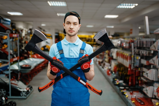 Travailleur masculin en uniforme détient deux axes dans le magasin d'outils. choix de matériel professionnel en quincaillerie, supermarché d'instruments