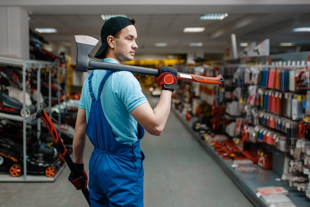 Travailleur masculin en uniforme détient deux axes, magasin d'outils